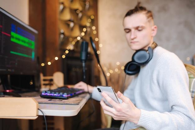 Jonge man belt naar een vriend zodat hij naar muziek luistert die hij zelf geïsoleerde man thuis opneemt