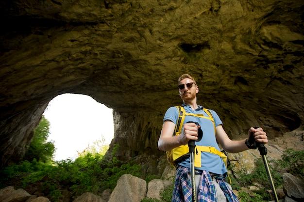 Jonge man bergbeklimmers door het gat in de stenen muren