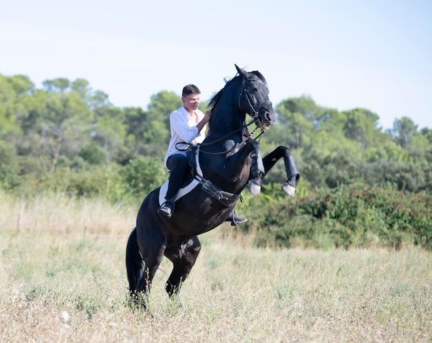 Jonge man berijden van een paard in de natuur