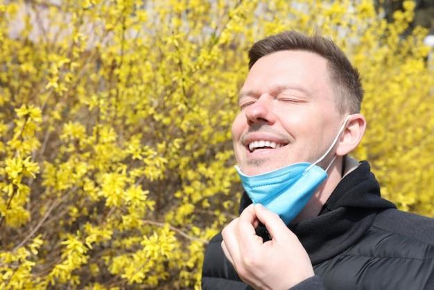 Jonge man beschermende gasmasker opstijgen van gezicht in de buurt van bloeiende boom
