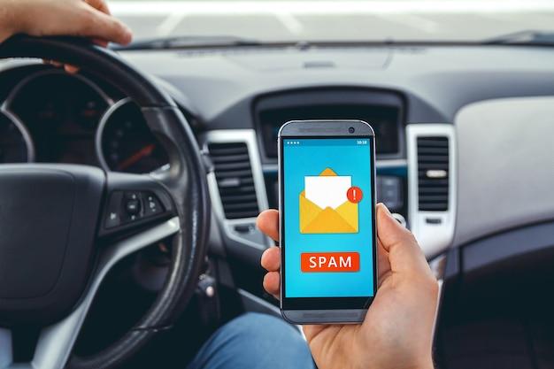 Jonge man besturen van een auto met een telefoon in zijn hand.