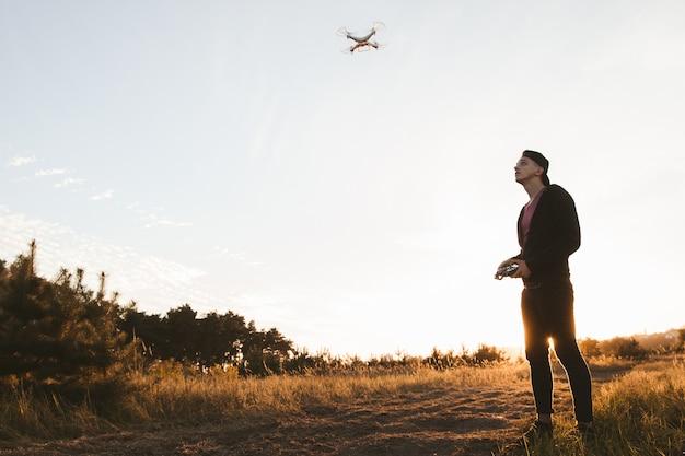 Jonge man besturen van rc drone buiten