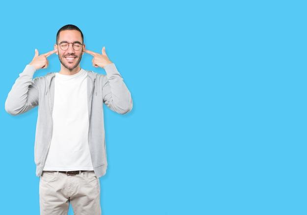 Jonge man bezorgd over harde geluiden en die zijn oren bedekken