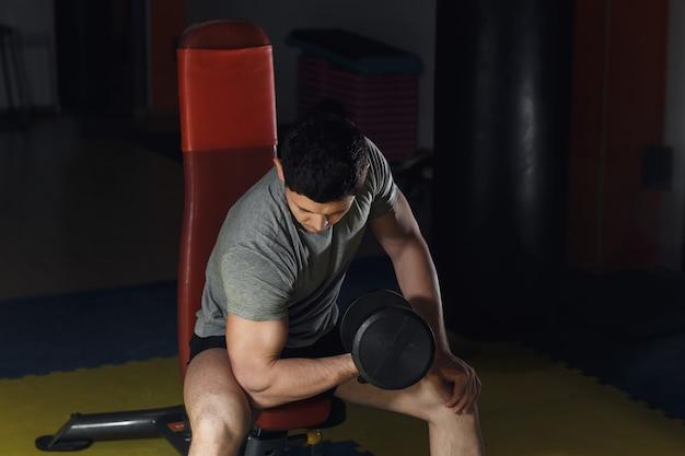 Jonge man biceps uit te werken - halter concentratie krullen.