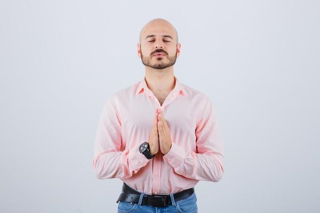 Jonge man bidden in roze shirt, spijkerbroek en hoopvol kijken, vooraanzicht.