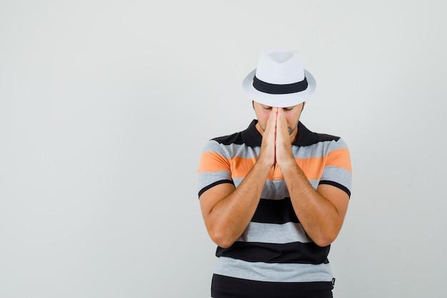 Jonge man biddend gebaar in gestreept t-shirt, hoed tonen en gefocust, vooraanzicht kijken. ruimte voor tekst