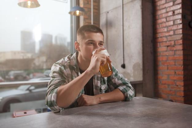Jonge man bier drinken in de pub alleen
