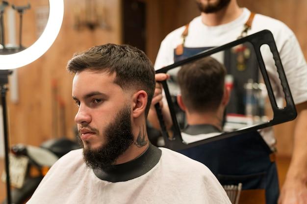 Jonge man bij de kapper die nieuw kapsel controleert