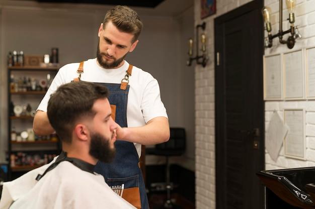 Jonge man bij de kapper wordt geknipt
