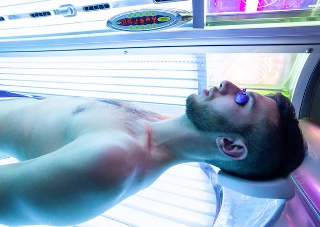 Jonge man bij solarium in schoonheidssalon.