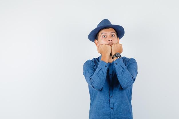Jonge man bijt emotioneel vuisten in blauw shirt, hoed en ziet er bang uit, vooraanzicht.