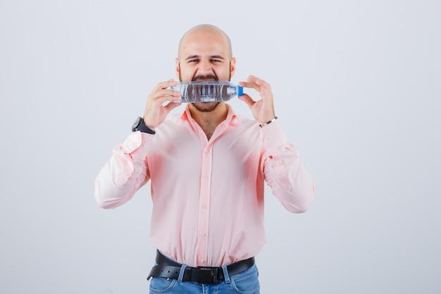 Jonge man bijt plastic fles in shirt, spijkerbroek en ziet er gek uit, vooraanzicht.