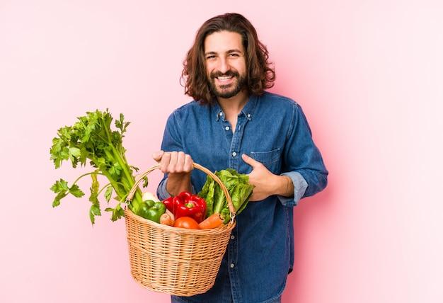 Jonge man biologische groenten plukken uit zijn tuin lachen en plezier maken.