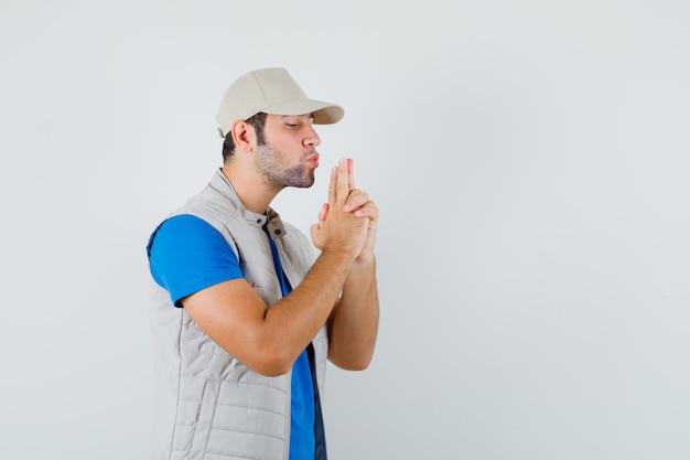 Jonge man blaast op vingerpistool in t-shirt, jasje, pet en kijkt zelfverzekerd. vooraanzicht.