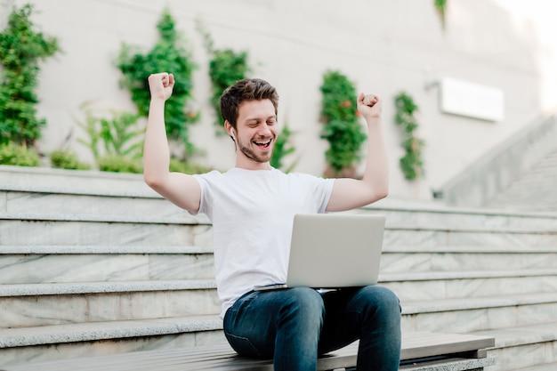 Jonge man blij met laptop voor freelance werk buitenshuis