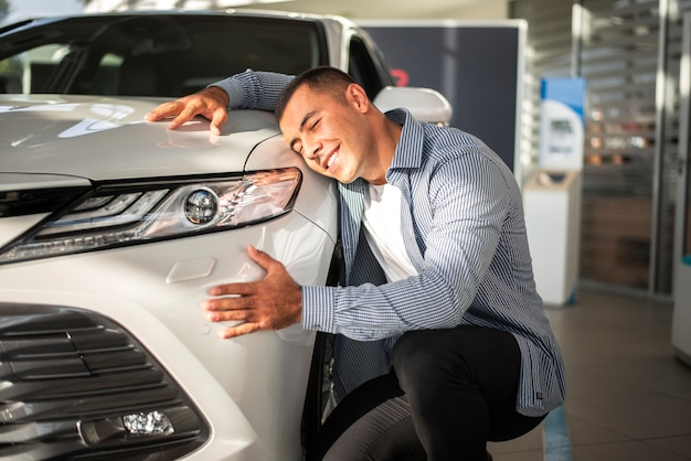 Jonge man blij voor zijn nieuwe auto