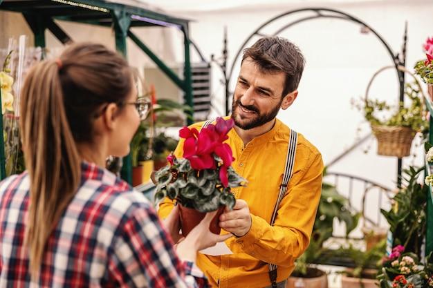 Jonge man bloemen kopen van vrouwelijke werknemer in de kwekerij.
