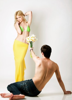 Jonge man bloemen presenteren aan blonde mooie vrouw in groene bikini en gele pareo op witte achtergrond in fotostudio. schoonheid en mode levensstijl concept