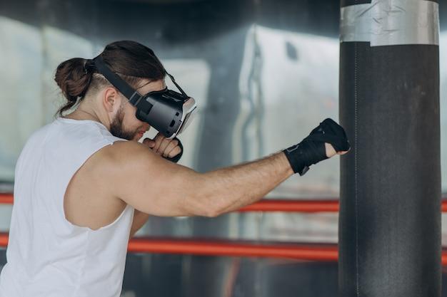 Jonge man bokser in vr 360 headset training voor schoppen in virtual reality-gevechten