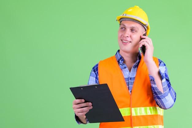 Jonge man bouwvakker tegen groene muur
