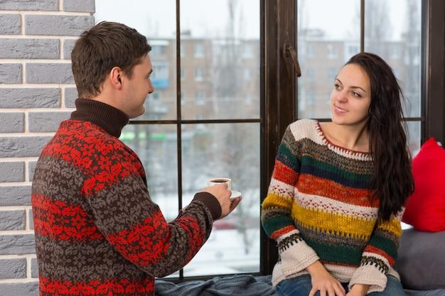 Jonge man bracht koffie naar zijn vrouw terwijl ze op de vensterbank zat met kussens en deken in de woonkamer