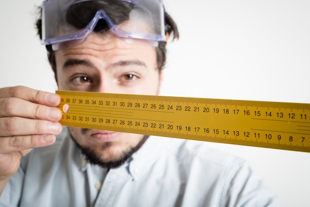 Jonge man bricolage werken meten met meter