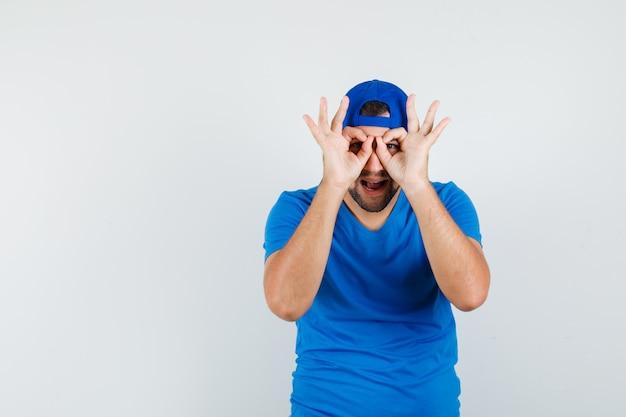 Jonge man bril gebaar in blauw t-shirt en pet tonen en grappig op zoek