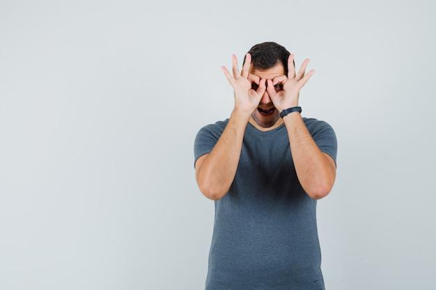 Jonge man bril gebaar in grijs t-shirt tonen en op zoek grappig