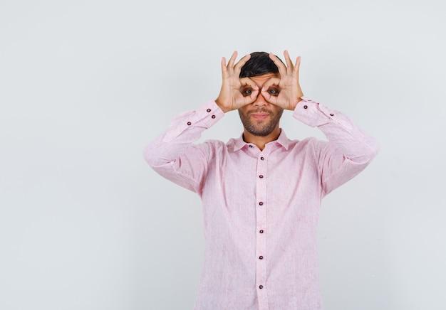 Jonge man bril gebaar in roze shirt tonen en op zoek grappig, vooraanzicht.
