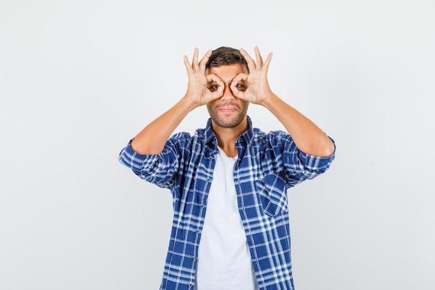 Jonge man bril gebaar in shirt tonen en op zoek grappig. vooraanzicht.