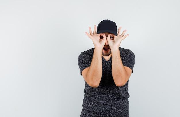 Jonge man bril gebaar in t-shirt en pet tonen en grappig kijken