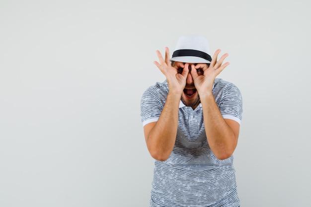 Jonge man bril gebaar in t-shirt, hoed tonen en op zoek grappig, vooraanzicht.