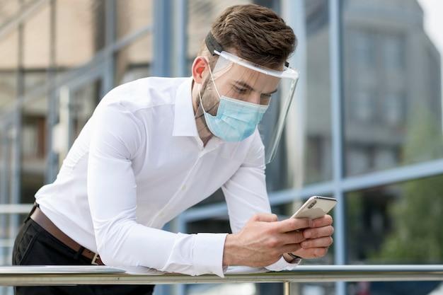 Jonge man buiten met masker mobiel controleren