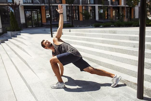 Jonge man buiten te oefenen. sta in yogapositie en houd een hand omhoog. zijn lichaam strekken en opwarmen voor het sporten. atleet buiten trainen bij stedelijk gebouw.