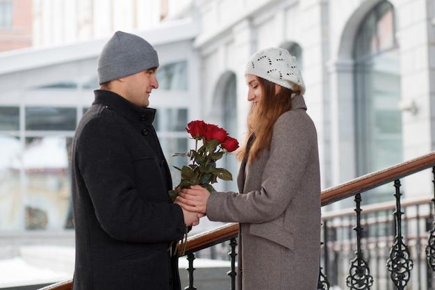 Jonge man cadeau zijn vriendin boeket rozen in de stad