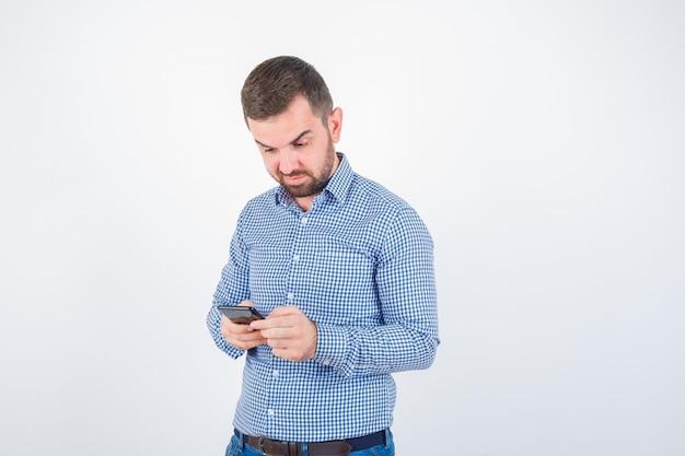 Jonge man chatten op mobiele telefoon in shirt, spijkerbroek en aarzelend. vooraanzicht.