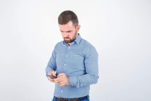 Jonge man chatten op mobiele telefoon in shirt, spijkerbroek en peinzend, vooraanzicht kijken.