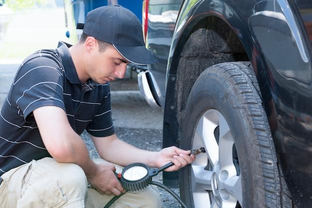 Jonge man controleert de bandenspanning van de auto