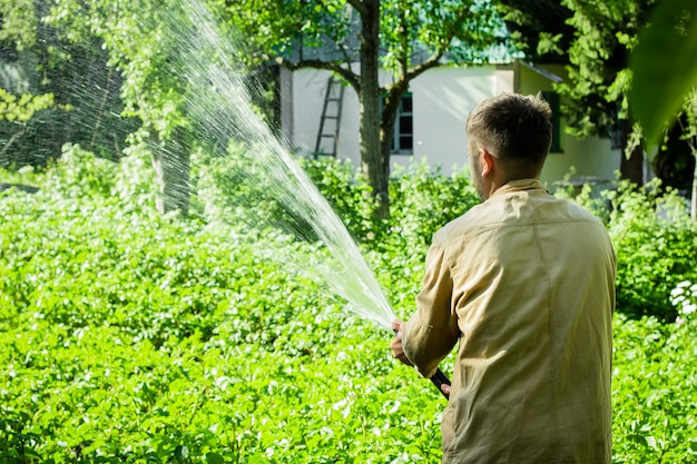 Jonge man de tuin water geven