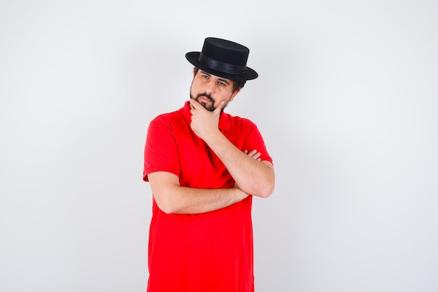 Jonge man denken in rood t-shirt, zwarte hoed en peinzend kijken, vooraanzicht.