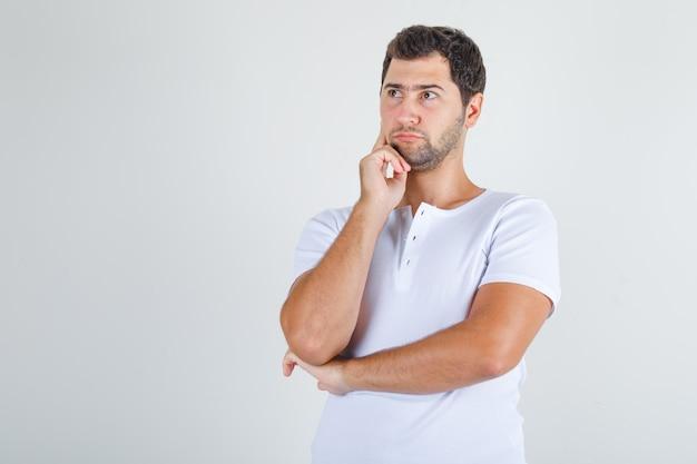 Jonge man denken met vinger op wang in wit t-shirt.