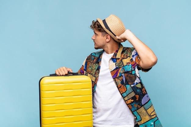 Jonge man denken of twijfelen, hoofd krabben, zich verbaasd en verward voelen, achter- of achteraanzicht. vakantie concept