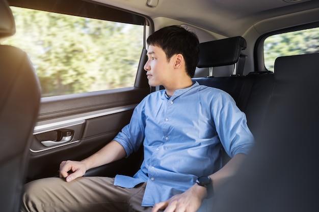 Jonge man denkt en kijkt uit het raam terwijl hij op de achterbank van de auto zit