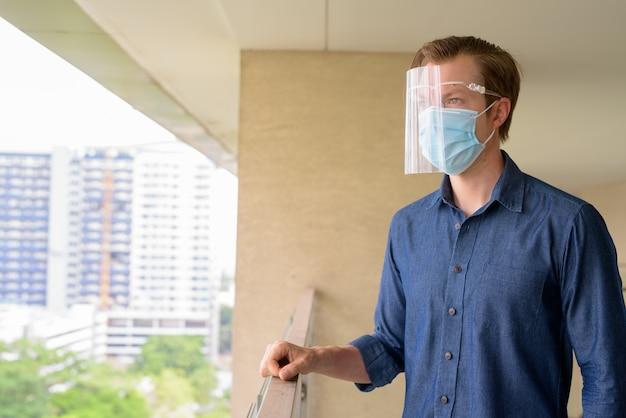 Jonge man denkt met masker en gelaatsscherm voor bescherming tegen de uitbraak van het coronavirus te zien op de stad