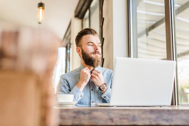 Jonge man dichtknopen shirt met kopje koffie advertentie laptop op bureau