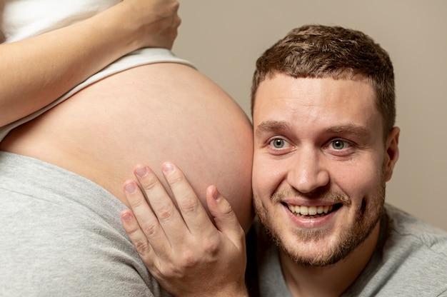 Jonge man die aan de buik van zijn zwangere vrouw luistert