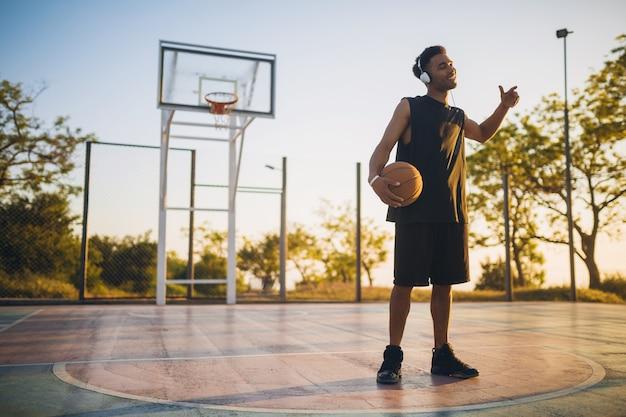 Jonge man die aan het sporten is, basketbal speelt bij zonsopgang, naar muziek luistert op een koptelefoon