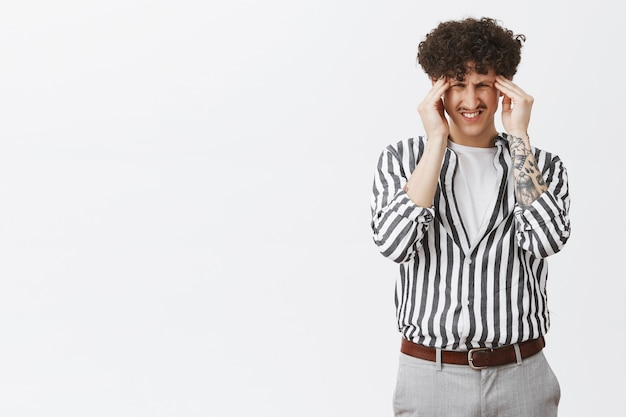 Jonge man die aan migraine lijdt, zich duizelig voelt of hoofdpijn heeft