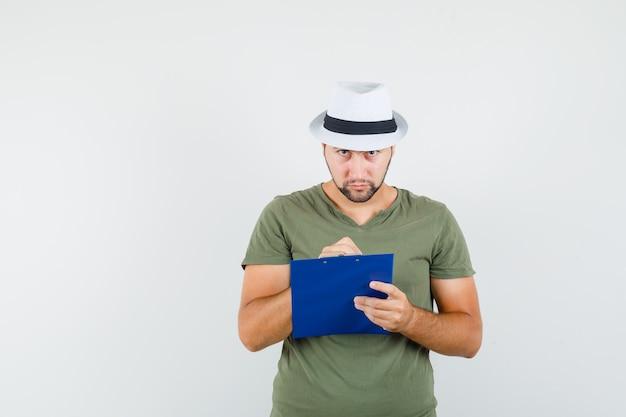 Jonge man die aantekeningen op klembord in groen t-shirt en hoed maakt en peinzend kijkt
