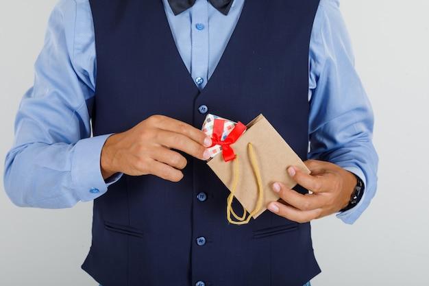 Jonge man die aanwezig is uit papieren zak in pak